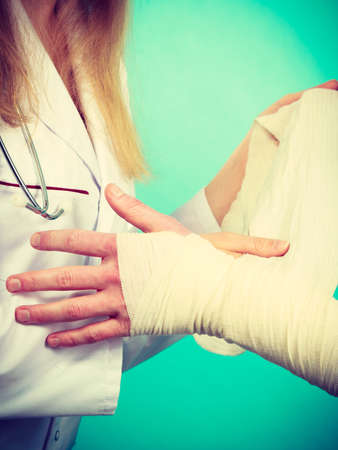 sprained: Female doctor bandaging male hand sprained wrist. Stock Photo