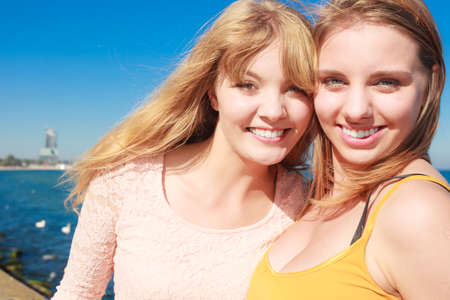 wind blowing: Two young women best friends blonde cheerful girls having fun outdoor wind blowing in hair. Stock Photo