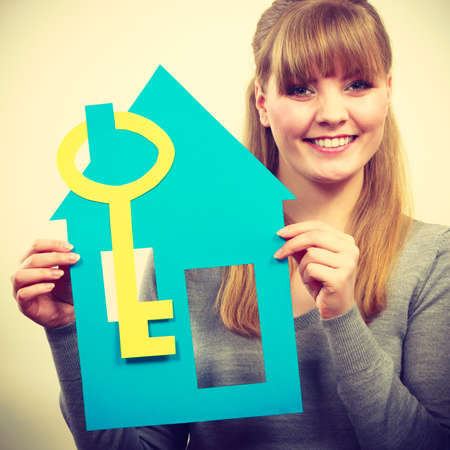 stabilization: Young joyful blonde woman with house and big key.