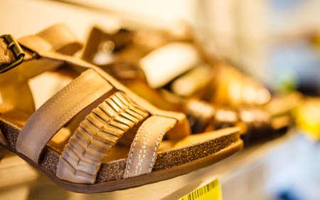 footgear: Closeup female sandals shoes in row on shop shelf