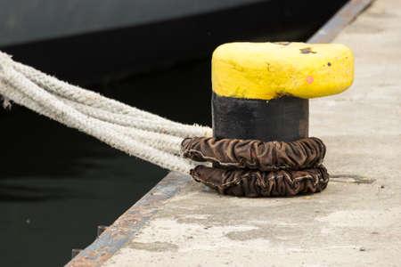 mooring bollard: Closeup yellow mooring bollard with rope in marina ship in the background Stock Photo