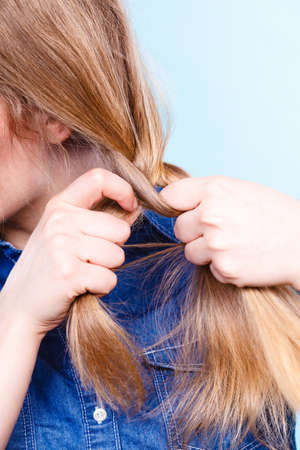 coiffeur: Hairstyle and hairdo. Haircare concept. Blonde woman playing with straight long hair. Hairstylist barber making braid tress coiffure.