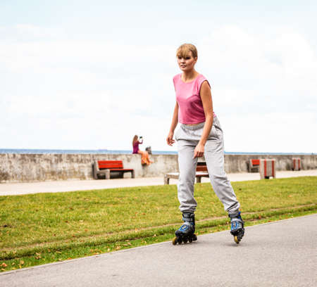 free riding: Outdoors activities sport and hobby.Wellbeing and exercising. Girl have fun riding rollerblades in park spending free time in summer. Stock Photo