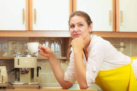 energizing: Pensive mature woman in apron holding cup of coffee in kitchen. Housewife female with hot energizing beverage. Caffeine energy.