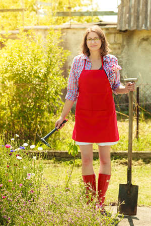 backyard woman: Middle age female with gardening tools outdoors. Woman standing with shovel in her backyard