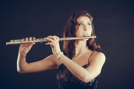Music and elegance. Alluring elegant woman playing on transverse flute. Female musician with her instrument performing. photo