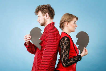heartbroken: Depressing heartbreak relationship problems concept. Heartbroken couple standing together. Man with lady turned their backs holding broken heart. Stock Photo