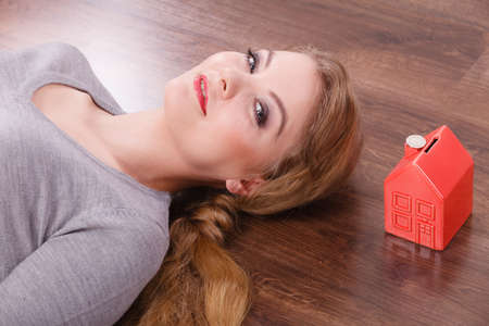 cash box: Home mortgage real estate property finances family concept. Woman lying with cash box. Young lady on floor next to piggy bank house.