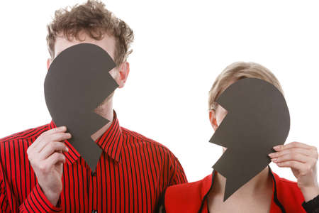 heartbreak: Love shame romance heartbreak depressing sadness relationship concept. Couple hiding their faces. Young man with woman holding broken heart parts in front of heads.