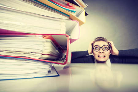 stack of paper: A lot of work and overwork concept. Terrified young businesswoman secretary with huge stack of binders. Scared accountant surrounded of to much work to do. Stock Photo
