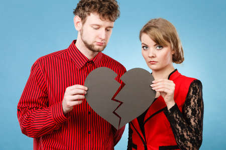 broken love: Relationship romance feelings sadness making up reconcillation concept. Young pair fixing heart. Lady with man reassembling broken love symbol together.