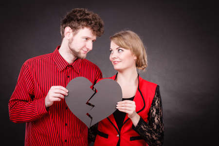 broken unity: Heal love concept. Couple woman and man holding two halves of broken heart fixed with plaster bandage going to be joined in one. Stock Photo