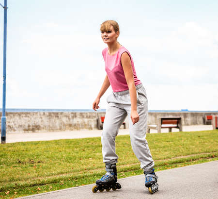 rollerskating: Active young woman in training suit outdoor rollerskating. Girl riding enjoying sport.