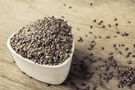 linseed: Healthy food diet. Brown flax seeds linseed in white bowl on wooden table Stock Photo