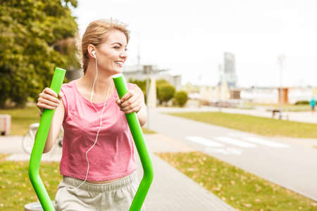 active listening: Active woman exercising on elliptical trainer machine listening to music. Fit sporty girl in training suit working out at outdoor gym. Sport fitness and healthy lifestyle concept.