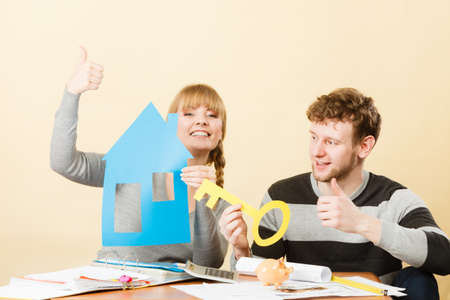 thumb keys: Dream and new plan for living. Young joyful smiling people thinking dreaming about their first house. Couple with big key to their future. Stock Photo