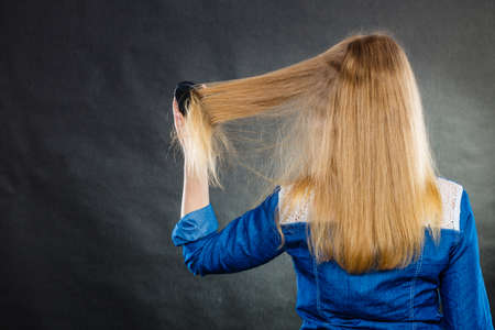 back straight: Everyday hygiene and care about good look. Back view of blonde casual girl combing her long straight hair. Woman using black comb hairbrush. Stock Photo