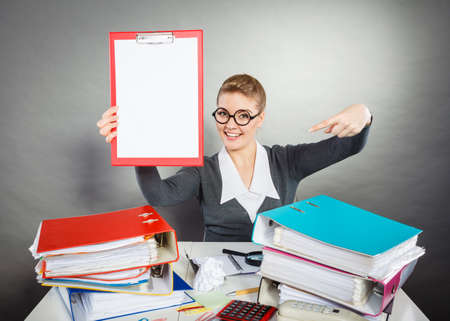 nerdy: Office nerdy job work documentation concept. Smiling woman pointing at binder. Young female gesturing at documents. Stock Photo