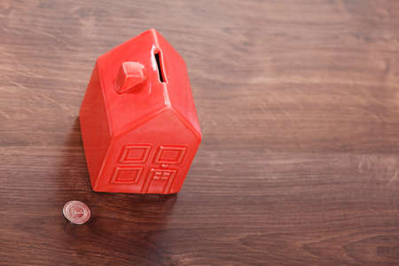cash box: Finance mortgage housing real estate savings concept. House like cash box. Piggy bank in home shape with coin.