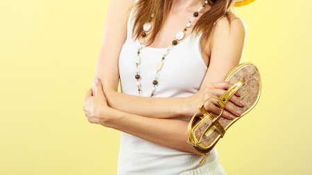 woman sandals: Holidays summer fashion concept. Woman holding golden sandals in hand yellow background.