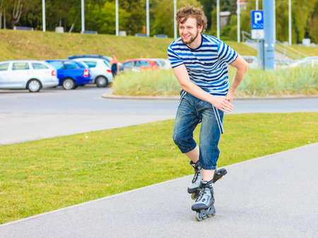 blading: Holidays, active lifestyle freedom concept. Young fit man on roller skates riding outdoors on street, guy rollerblading on sunny day