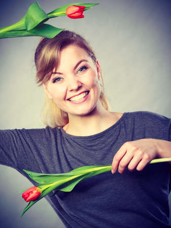 craze: Spring time. Craziness and fun concept. Playful happy girl playing with flowers. Joyful smiling funny positive female person making crazy figures with tulips. Stock Photo