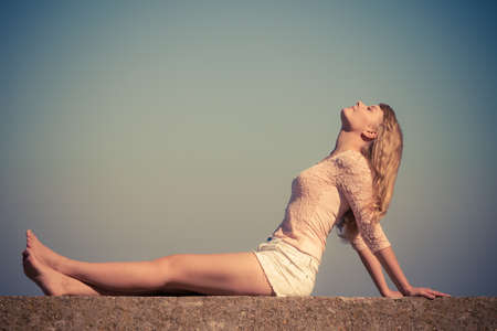 ragazze a piedi nudi: Vacanze, l'estate e il concetto di libertà. Bella ragazza bionda di riposo all'aperto godendo luce solare filtrata foto