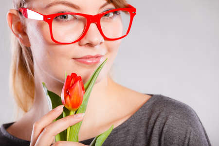 lady in red: Beauty emotions nature passion glasses concept. Nerdy girl snffing flower. Young blonde casual lady holding smelling red tulip. Stock Photo