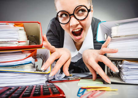 anger management: Workaholism mental insanity weird job work company concept. Insane office woman at work. Mad secretary making silly expression lurking through her desk.