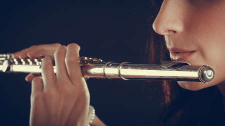 soloist: Music and elegance. Alluring elegant woman playing on transverse flute. Female musician with her instrument performing.