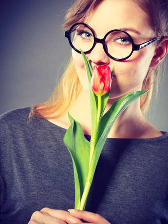 enjoyable: Peace and content. Beauty adorable girl smelling beautiful spring flower. Peaceful enjoyable woman with red green tulip. Lady smell nature. Stock Photo