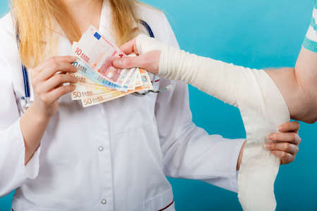 doctor money: Corruption in healthcare industry. Female doctor bandaging male hand. Man giving money to woman. Bribery in medicine. Stock Photo