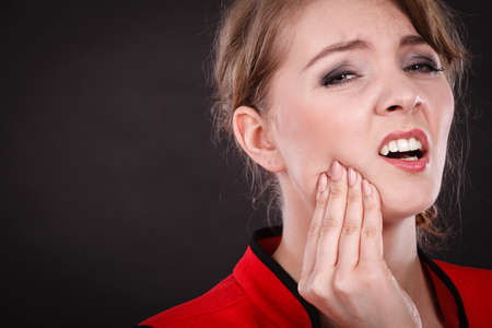 abscess: Stress and pain. Face of young painful woman. Female feeling tooth pain ache. Girl touching her mouth teeth by hand. Stock Photo