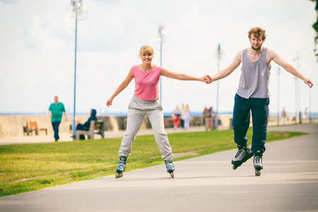 rollerskating: Active young people friends in training suit rollerskating outdoor. Woman and man couple holding hands riding enjoying sport.