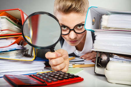 workaholic: Attention paperwork corporate details workaholism concept. Crazy office lady at desk. Workaholic secretary holding magnifying glass.