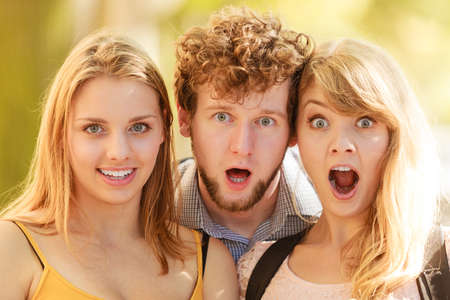 Three surprised astonished young people friends outdoor. Attractive women and handsome man portrait. Summer vacation.