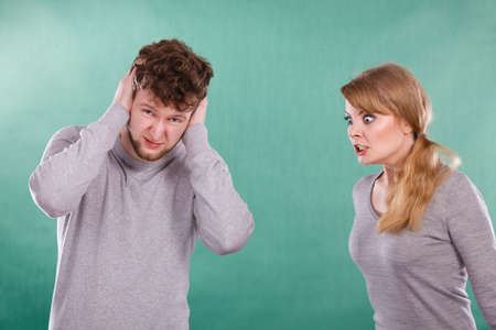 afraid man: Violence against man. Aggressive woman yelling shouting on scared afraid man. Negative relations in partnership. Expressive young lady screaming.