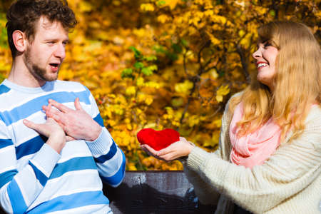 confess: Accepting and sharing feelings. Confessing love and affection with romantic gesture. Positive reaction. Pair sit on bench in park woman present plush heart toy to man. Stock Photo