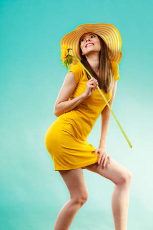 pretty dress: portrait of attractive summer woman in yellow hat with sunflower in hand on blue background
