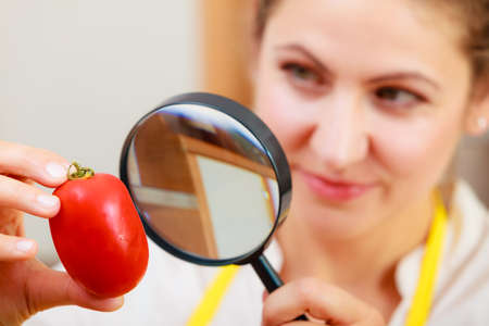 food testing: Mature woman female inspecting testing tomato food with magnifying glass.