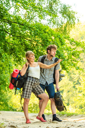 tramping: Adventure, tourism, enjoying summer time together - Hiking young couple with guitar backpack tramping on forest road sunny countryside Stock Photo