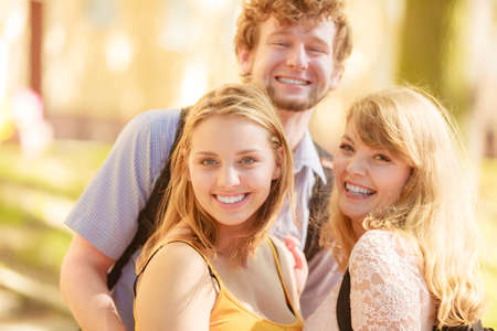 women friendship: Happy smiling young people friends outdoor. Attractive women and handsome man. Summer vacation. Stock Photo