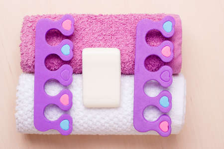 bar of soap: Foot care and cosmetics. Pedicure accessories set tools, two toe separators with bar soap on towels