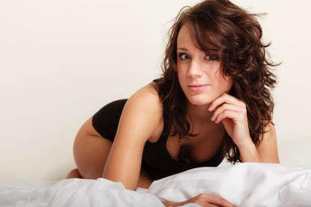Sexy girl paresseux en noir sous-vêtements du corps allongé sur le lit. Jeune femme de détente farniente dans sa chambre au matin.