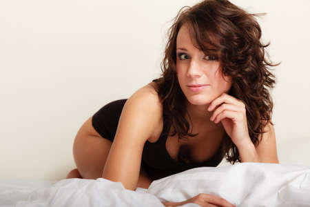 pretty brunette woman: Sexy lazy girl in black body underwear lying on the bed. Young woman relaxing lazing in her bedroom at the morning.