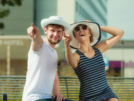 enjoying life: Tourists couple sitting on city bench resting. Happy woman and man enjoying life summer vacation outdoor