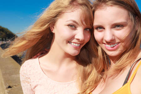 wind blowing: Two young women best friends blonde cheerful girls having fun outdoor wind blowing in hair. Summer happiness friendship concept.