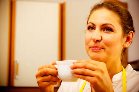 energizing: Mature woman drinking cup of coffee in kitchen. Housewife female with hot energizing beverage. Caffeine energy. Stock Photo