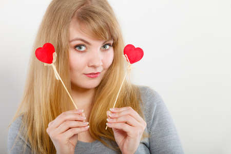 enjoyable: Love and fun concept. Lovely enjoyable smiling woman playing with two little red hearts on sticks. Playful joyful attractive blonde girl portrait. Stock Photo