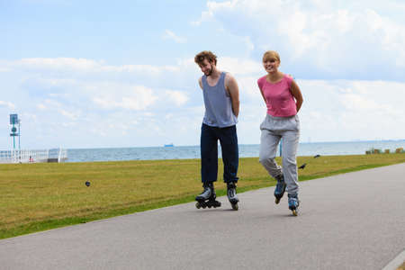rollerblades: Love dating leisure romance relax concept. Cheerful couple enjoying ride together. Young girl and boy skating on rollerblades in park near sea.
